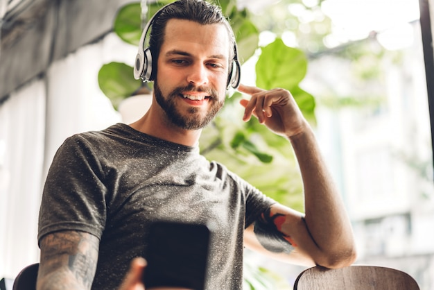 Przystojny brodaty modnisia mężczyzna relaksuje słuchać muzyka z hełmofonami i kawą przy stołem w kawiarni komunikaci i technologii pojęcie