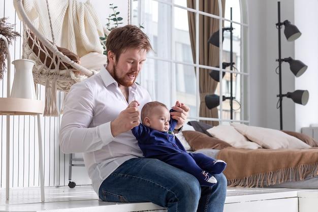 Przystojny brodaty ojciec bawi się ze swoim małym chłopcem w pięknym wnętrzu