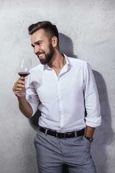 Przystojny brodaty sommelier degustuje czerwone wino