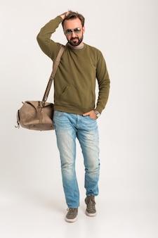 Przystojny brodaty stylowy mężczyzna pozowanie na białym tle ubrany w bluzę z torbą podróżną, na sobie dżinsy i okulary przeciwsłoneczne