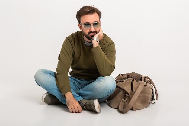 Przystojny brodaty stylowy mężczyzna siedzi na podłodze na białym tle ubrany w bluzę z torbą podróżną, na sobie dżinsy i okulary przeciwsłoneczne, smutny i zmęczony czekanie
