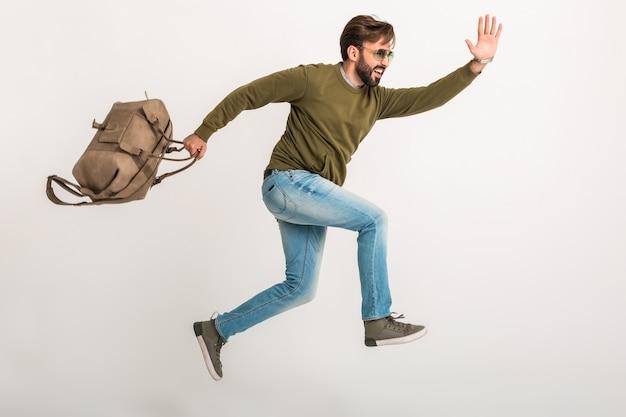 Przystojny brodaty stylowy mężczyzna skacze bieganie na białym tle ubrany w bluzę z torbą podróżną, w dżinsach i okularach przeciwsłonecznych, szalony podróżnik w pośpiechu