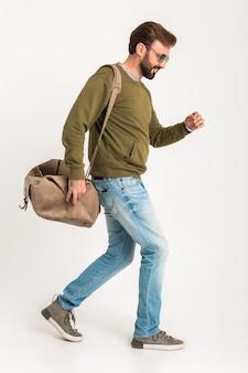 Przystojny brodaty stylowy mężczyzna spaceru na białym tle ubrany w bluzę z torbą podróżną, na sobie dżinsy i okulary przeciwsłoneczne