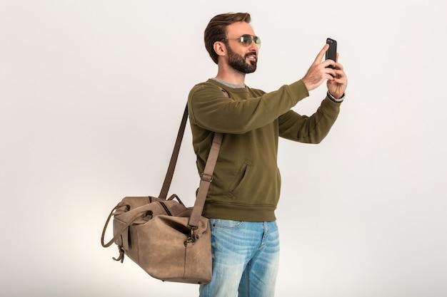 Przystojny brodaty stylowy mężczyzna w bluzie z torbą podróżną, na sobie dżinsy i okulary przeciwsłoneczne na białym tle biorąc selfie zdjęcie na telefon
