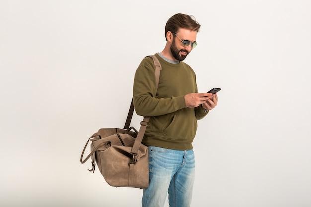Przystojny brodaty stylowy mężczyzna w bluzie z torbą podróżną, na sobie dżinsy i okulary przeciwsłoneczne na białym tle trzymając telefon