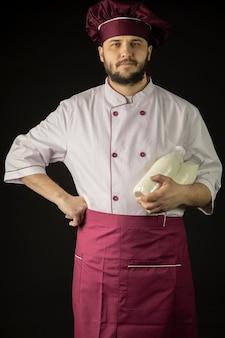 Przystojny brodaty szefa kuchni mężczyzna w mundurze trzyma dwie butelki z mlekiem