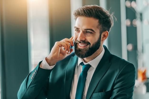 Przystojny brodaty uśmiechnięty biznesmen opowiada na telefonie w formalnej odzieży podczas gdy siedzący w bufecie.