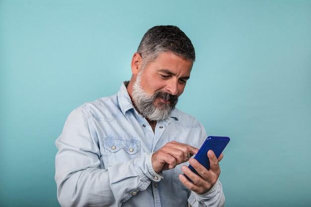 Przystojny brodaty uśmiechnięty mężczyzna używający smartfona do kontaktu z rodziną i przyjaciółmi na białym tle na niebieskim tle