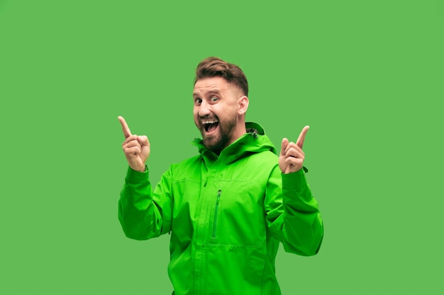 Przystojny brodaty uśmiechnięty szczęśliwy młody człowiek patrząc z przodu na białym tle na żywe modne zielone studio