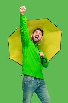 Przystojny brodaty uśmiechnięty szczęśliwy młody człowiek trzyma parasol i patrząc na kamery na białym tle na żywe modne zielone studio.