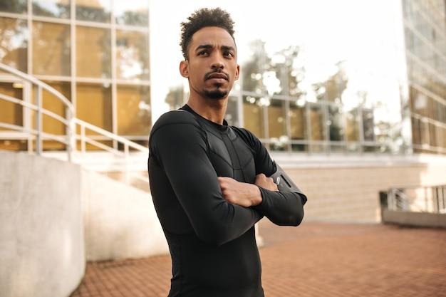 Przystojny brunet ciemnoskóry mężczyzna w czarnej spódnicy z długimi rękawami ze skrzyżowanymi ramionami