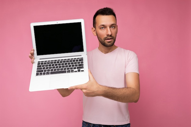 Przystojny brunet mężczyzna posiadający laptopa patrząc na kamery w t-shirt na na białym tle różowy.