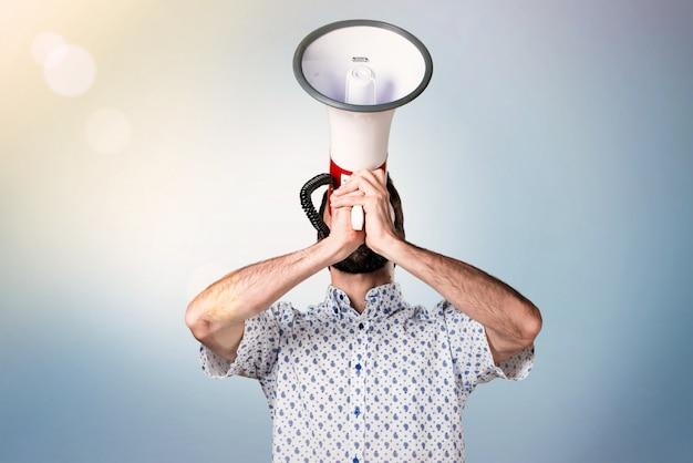 Przystojny brunetka mężczyzna krzyczy megafonem z brodą
