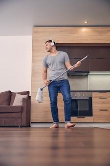 Przystojny brunetka mężczyzna w zwykłych ubraniach ze słuchawkami myje podłogę kijem do mopa