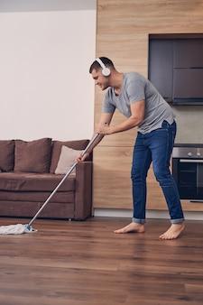 Przystojny brunetka mężczyzna w zwykłych ubraniach ze słuchawkami myje podłogę podczas słuchania muzyki