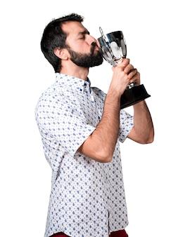 Przystojny brunetka mężczyzna z brodą trzyma trofeum