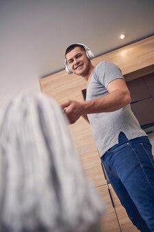 Przystojny brunetka mężczyzna z dużymi słuchawkami wskazującymi na aparat fotograficzny ścierką do podłogi i śmiejącym się