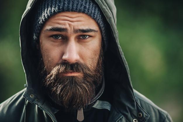 Przystojny brutalny brodaty mężczyzna z ciemną brodą i wąsami ubrany w zimowe ubrania
