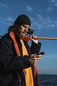 Przystojny brutalny brodaty rybak w płaszczu stojący z wędką nad brzegiem morza, korzystający z telefonu komórkowego