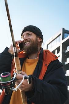 Przystojny, brutalny brodaty rybak w płaszczu stojący z wędką nad brzegiem morza, rozmawiający przez telefon komórkowy