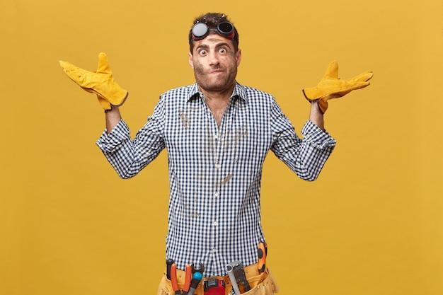 Przystojny brygadzista w kraciastej koszuli, okularach i rękawiczkach ochronnych z paskiem z narzędziami, wzrusza ramionami, nie wiedząc, gdzie jest pęknięcie. pracownik fizyczny ma wątpliwości podczas pracy