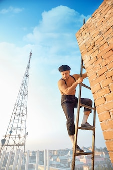 Przystojny budowniczy z nagim torsem w kapeluszu wspina się po drabinie i patrzy w dół. drabina oparta o ceglany mur w nieukończonym budynku. wysoka wieża telewizyjna na tle.