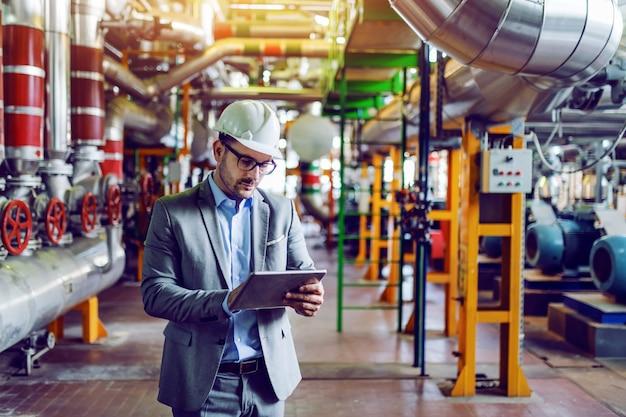 Przystojny caucasian kierownik w popielatym kostiumu z hełmem na głowie i używać pastylkę podczas gdy stojący w elektrowni.