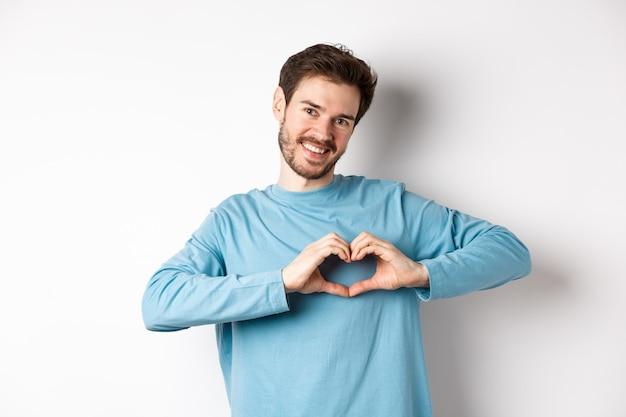 Przystojny chłopak mówi kocham cię, pokazując gest serca i uśmiechając się do kamery, wyrażaj miłość i romantyczne uczucie, stojąc na białym tle