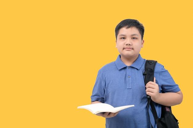 Przystojny chłopak student niosąc tornister i trzymając książkę