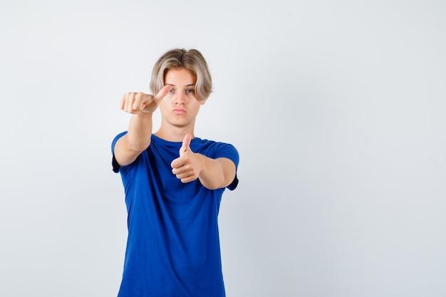 Przystojny chłopak teen pokazuje podwójne kciuki w niebieskim t-shirt i wygląda pewnie. przedni widok.