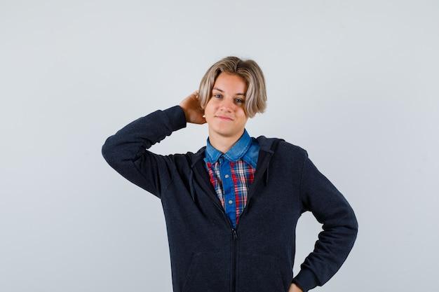 Przystojny chłopak teen trzymając rękę za głowę w koszuli, bluzie z kapturem i patrząc wesoło. przedni widok.