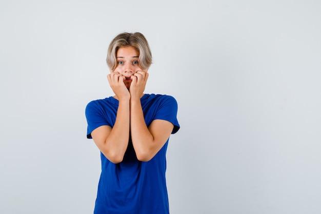 Przystojny chłopak teen w niebieskiej koszulce, trzymając ręce na policzkach i patrząc przestraszony, widok z przodu.