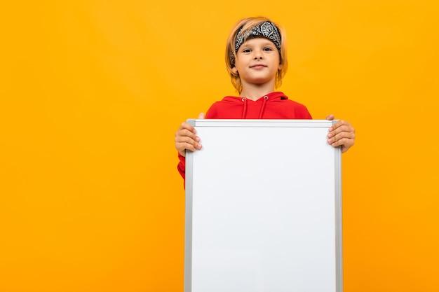 Przystojny chłopak w czerwonej bluzie i czarnej chustce na żółtym tle z tablicą magnetyczną do tekstu z uśmiechem patrzy w kamerę