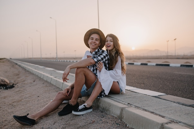 Przystojny chłopak w kapeluszu i kobieta w białej bluzce vintage siedzi razem na drodze i cieszy się piękny zachód słońca. urocza długowłosa młoda kobieta odpoczywa w pobliżu autostrady ze swoim chłopakiem