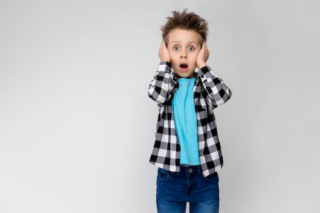 Przystojny chłopak w kraciastej koszuli, niebieskiej koszuli i dżinsach stoi na szarym. chłopiec otworzył usta i zakrył uszy rękami