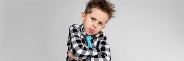 Przystojny chłopak w kraciastej koszuli, niebieskiej koszuli i dżinsach stoi na szarym tle.