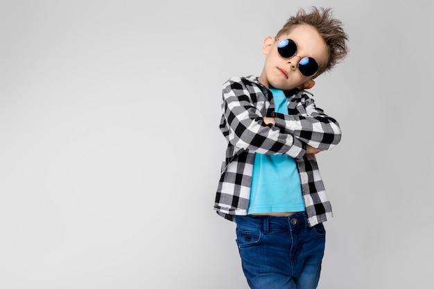 Przystojny chłopak w kraciastej koszuli, niebieskiej koszuli i jeansach stoi. chłopiec ma na sobie okrągłe okulary. rudowłosy chłopak skrzyżował ręce na piersi