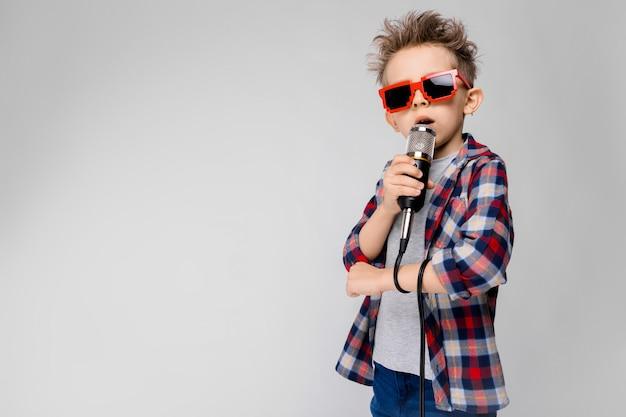 Przystojny chłopak w kraciastej koszuli, szarej koszuli i dżinsach stoi na szarym tle. chłopiec w okularach przeciwsłonecznych. rudy chłopiec śpiewa do mikrofonu