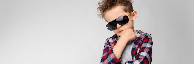 Przystojny chłopak w kraciastej koszuli, szarej koszuli i jeansach stoi. chłopiec w czarnych okularach przeciwsłonecznych. chłopiec trzyma rękę na brodzie