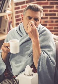 Przystojny chory dojrzały mężczyzna pije gorącej herbaty.