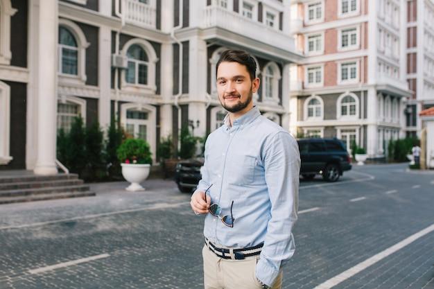 Przystojny ciemnowłosy mężczyzna w niebieskiej koszuli spaceruje po brytyjskiej dzielnicy. trzyma okulary przeciwsłoneczne