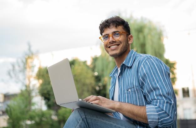 Przystojny copywriter korzystający z laptopa,