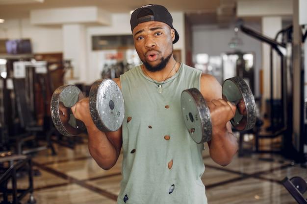 Przystojny czarny człowiek jest zaangażowany w siłownię
