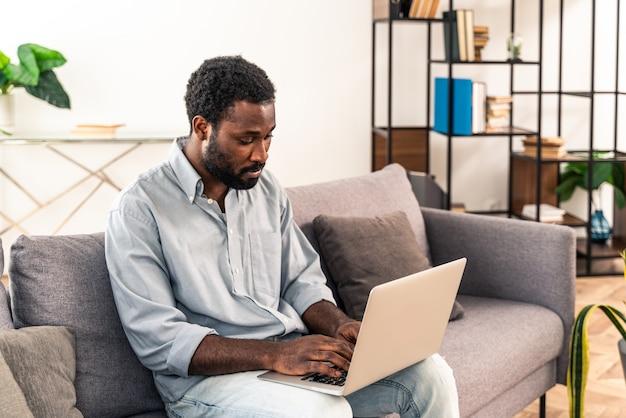 Przystojny czarny dorosły mężczyzna pracujący z laptopem w domu