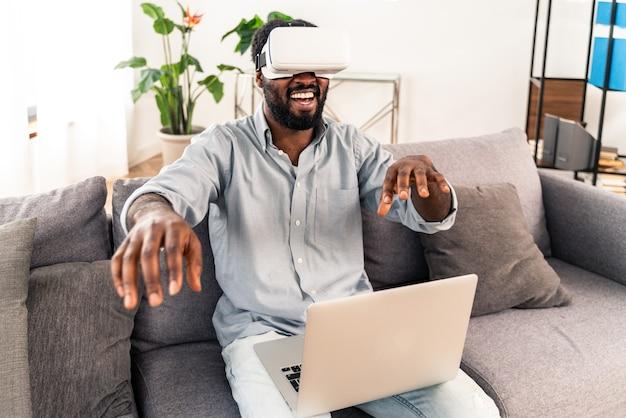 Przystojny czarny dorosły mężczyzna w domu bawi się zestawem słuchawkowym vr
