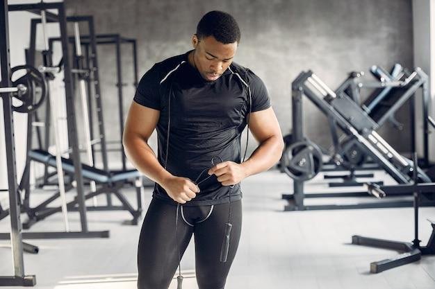 Przystojny czarny mężczyzna jest zaangażowany w siłownię