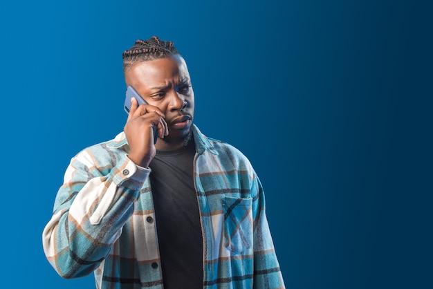 Przystojny czarny mężczyzna rozmawia przez telefon martwi się. w połowie strzału. niebieskie tło.