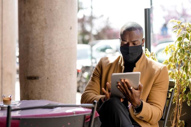 Przystojny czarny mężczyzna w eleganckim, stylowym garniturze, siedząc w stoliku przy użyciu tabletu. facet nosi maskę.