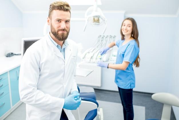 Przystojny dentysta z młodą asystentką w mundurze przygotowującym się do pracy w gabinecie stomatologicznym