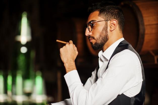 Przystojny dobrze ubrany mężczyzna arabski ze szklanką whisky i cygarem postawiony w pubie.